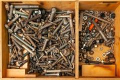 Drewniany pudełko z wiązką dokrętki, rygle i śruby, zdjęcie royalty free