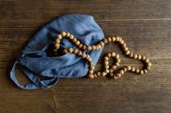 Drewniany różaniec Drewniany różaniec w błękitnej torbie na drewnianej podłoga zdjęcia royalty free
