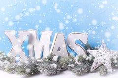 Drewniany słowa Xmas, gałąź futerkowy drzewo i dekoracyjna gwiazda na błękitnym, Fotografia Royalty Free