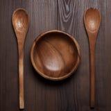 Drewniany sałatkowy puchar i dwa łyżki na stole zdjęcia royalty free
