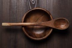 Drewniany sałatkowy talerz i łyżka na brązu stole fotografia stock