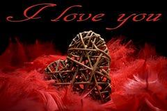Drewniany serce w czerwonych piórkach Obrazy Royalty Free