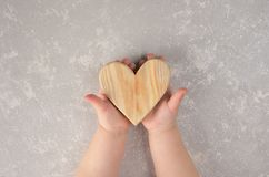 Drewniany serce w dziecko rękach to walentynki dni abstrakcyjny tło zdjęcia stock