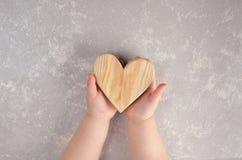 Drewniany serce w dziecko rękach to walentynki dni abstrakcyjny tło zdjęcie stock