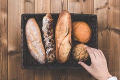 Drewniany stół, chleb i ręki Zdjęcie Stock