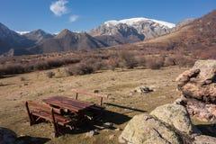 Drewniany stół i ławki dla turysty odpoczynku strefy przy śladem Botev osiągamy szczyt Środkowy Balkan park narodowy, Stara plani zdjęcia stock