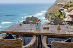 Drewniany stół i krzesła przy plenerową falezy kawiarnią zdjęcie stock