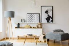 Drewniany stół i popielaty pouf w jaskrawym płaskim wnętrzu z plakatami Fotografia Royalty Free