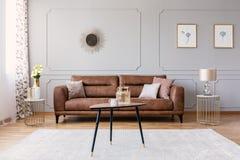Drewniany stół na dywanie przed rzemienną kanapą w popielatym płaskim wnętrzu z plakatami i lustrem obrazy royalty free