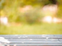 Drewniany stół na zielonym zamazanym tle Zdjęcia Royalty Free