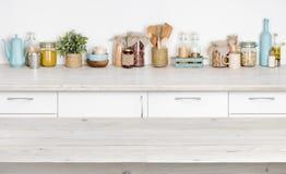Drewniany stół nad zamazaną kuchenną meblarską półką z karmowymi składnikami obraz royalty free
