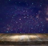 Drewniany stół przed błyskotliwością zaświeca tło Obrazy Royalty Free
