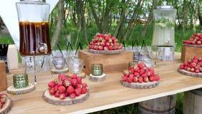 Drewniany stół z świeżymi truskawkami, miotacz zamrażał herbaty od cytryny, bezalkoholowy mojito, świąteczny stół z fundami zbiory wideo