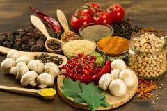 Drewniany stół z kolorowymi pikantność, ziele i warzywami, zdjęcie stock