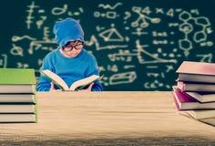 Drewniany stół z stosem książki i chłopiec czyta książkę z zdjęcia stock