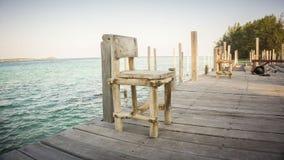 Drewniany stary wietrzejący krzesło na małym porcie z dennym tło krajobrazem Indonesia zdjęcie royalty free