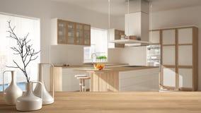 Drewniany stołowy wierzchołek lub półka z minimalistic nowożytnymi wazami nad zamazaną minimalistyczną nowożytną kuchnią, biały a zdjęcia stock