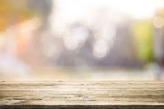 Drewniany stołowy wierzchołek na bokeh abstrakta tle Obrazy Stock