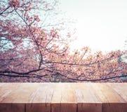 Drewniany stołowy wierzchołek na plamy Sakura kwiacie w ogrodowym tle Natura obraz stock