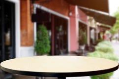 Drewniany stołowy wierzchołek na plamy tle sklep z kawą & x28; lub restaurant& x29; Zdjęcie Royalty Free