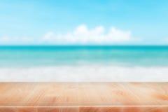 Drewniany stołowy wierzchołek na zamazanym błękitnym morzu i biały piasek wyrzucać na brzeg backgrou Obraz Stock