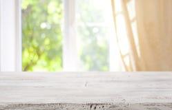 Drewniany stołowy wierzchołek na zamazanym nadokiennym tle dla produktu pokazu fotografia stock