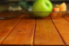 Drewniany stołowy wierzchołek na zamazanym owocowym tle - może używać dla montażu lub wystawiać twój produkty obraz stock