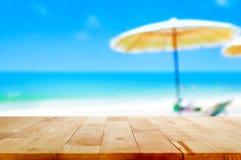 Drewniany stołowy wierzchołek na zamazanym plażowym tle Zdjęcia Royalty Free