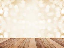Drewniany stołowy wierzchołek nad abstrakcjonistycznym złotym tłem z białym bokeh dla bożych narodzeń i nowy rok wakacji Montażu  fotografia stock