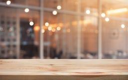 Drewniany stołowy wierzchołek z lekką złocistą kawiarnią, restauracyjny tło zdjęcia stock