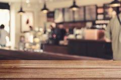 Drewniany stołowy wierzchołek z zamazanym wizerunku barem w sklep z kawą Fotografia Royalty Free