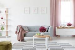 Drewniany stolik do kawy z świeżym wrzosem i owoc na talerzu w istnej fotografii jaskrawy siedzącego pokoju wnętrze z plakatami n obrazy stock