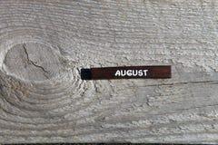 Drewniany sześcian z imieniem miesiąc przy starą deską augusta Obrazy Royalty Free