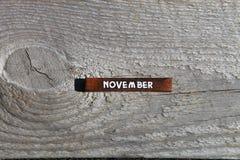 Drewniany sześcian z imieniem miesiąc przy starą deską Novembe Zdjęcia Stock
