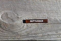 Drewniany sześcian z imieniem miesiąc przy starą deską Septemb Obrazy Stock