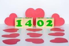 Drewniany sześcian z inskrypcją 14 Luty i czerwoni serca kształtujemy Obraz Stock