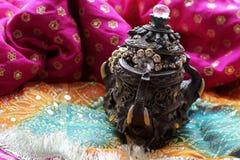 Drewniany szkatuły pudełko z orientalnymi wzorów słoniami pełno złocista biżuteria na Malinowym tkaniny tle zdjęcia stock