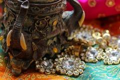 Drewniany szkatuły pudełko z orientalnymi wzorów słoniami pełno złocista biżuteria na Malinowym tkaniny tle obrazy royalty free