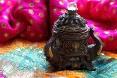 Drewniany szkatuły pudełko z orientalnymi wzorów słoniami pełno złocista biżuteria na Malinowym tkaniny tle obraz royalty free