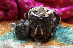 Drewniany szkatuły pudełko z orientalnymi wzorów słoniami pełno złocista biżuteria na Malinowym tkaniny tle obrazy stock