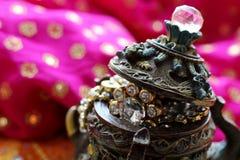 Drewniany szkatuły pudełko z orientalnymi wzorów słoniami pełno złocista biżuteria na Malinowym tkaniny tle zdjęcie stock