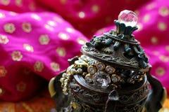 Drewniany szkatuły pudełko z orientalnymi wzorów słoniami pełno złocista biżuteria na Malinowym tkaniny tle fotografia stock