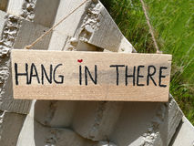 Drewniany szyldowy zrozumienie w tam wieszać na kamiennej ścianie z sercem jak Obraz Stock