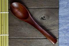 Drewniany tło i łyżka na niebiescy dżinsy teksturze. Zdjęcia Stock