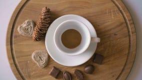 Drewniany tło nalewać gorącą kawę, cukierki i ciastko w 4K, zbiory wideo