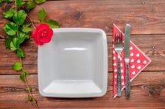 Drewniany tło z czerwieni tableware i różą Zdjęcia Stock
