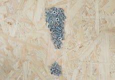 Drewniany tło z małymi metal częściami Fotografia Stock