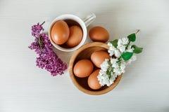 Drewniany talerz i Ceramiczna filiżanka z jajkami, bielem i Purpurowymi gałąź bez, biały tła drewniane Odgórny widok Obrazy Royalty Free
