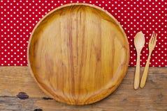 Drewniany talerz, tablecloth, łyżka, rozwidlenie na stołowym tle Fotografia Royalty Free