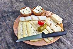 Drewniany talerz z wyborem sery, pomidor, zalewa i nóż na drewnianym stole, Obraz Stock